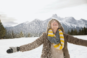 Snow falling around exuberant woman with arms outstretchedの写真素材 [FYI02273065]
