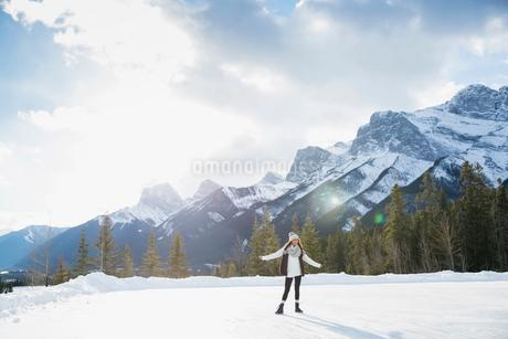 Woman ice skating below snowy mountainの写真素材 [FYI02273096]