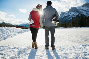 Couple with ice skates hugging below snowy mountainの写真素材 [FYI02273142]