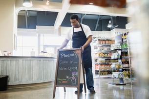 Worker placing blackboard in grocery storeの写真素材 [FYI02273382]