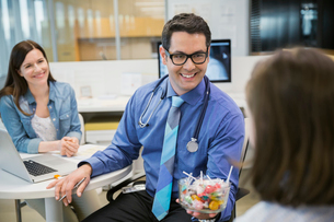 Pediatrician giving candy to girl in clinic officeの写真素材 [FYI02273543]