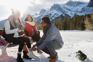 Family putting on ice skates below snowy mountainの写真素材 [FYI02273798]