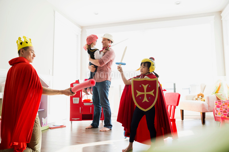 Father and daughter in costumes playing sword fightの写真素材 [FYI02273888]