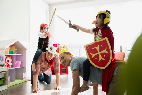 Fathers piggybacking daughters in costumes playing sword fightの写真素材 [FYI02273901]