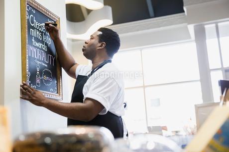 Grocery business owner writing on blackboardの写真素材 [FYI02273933]