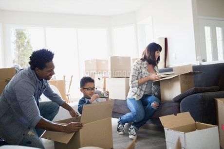 Family unpacking moving boxes in living roomの写真素材 [FYI02273999]