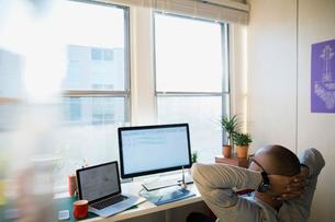 Designer with hands behind head in officeの写真素材 [FYI02274236]