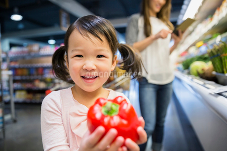 Portrait of smiling girl holding red bell pepperの写真素材 [FYI02274354]