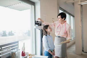 Pediatrician measuring girls weight on scale in clinicの写真素材 [FYI02274460]