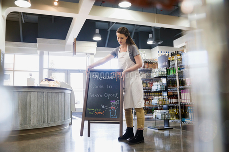 Worker placing blackboard in grocery storeの写真素材 [FYI02274516]