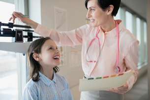 Pediatrician measuring girls weight on scale in clinicの写真素材 [FYI02274520]