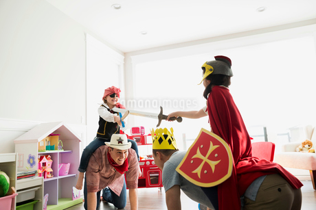 Fathers piggybacking daughters in costumes playing sword fightの写真素材 [FYI02274695]
