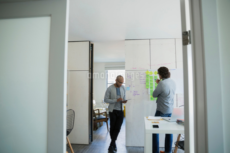 Businessmen brainstorming with adhesive notes in officeの写真素材 [FYI02274867]