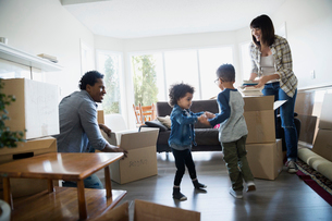 Family unpacking moving boxes in living roomの写真素材 [FYI02274946]