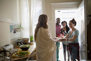 Woman greeting friends arriving for potluck dinner partyの写真素材 [FYI02274962]