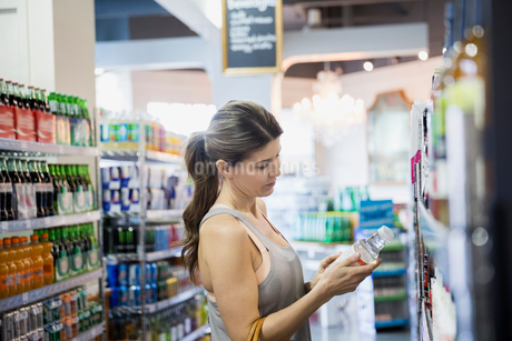 Woman reading label on bottle in grocery storeの写真素材 [FYI02275076]