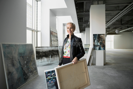 Portrait confident artist carrying paintings in art galleryの写真素材 [FYI02275395]
