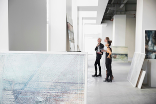 Artist and art dealers examining paintings art galleryの写真素材 [FYI02275453]