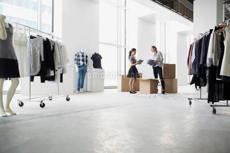 Fashion stylists unpacking clothing in studioの写真素材 [FYI02275480]