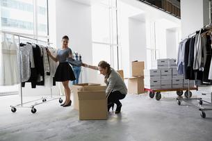 Fashion stylists unpacking clothing in studioの写真素材 [FYI02275493]