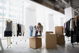 Fashion stylist unpacking clothing in studioの写真素材 [FYI02275498]