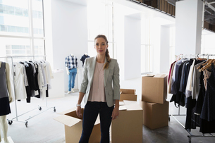 Portrait confident fashion stylist unpacking clothing in studioの写真素材 [FYI02275527]