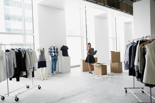 Fashion stylist talking on cell phone unpacking clothingの写真素材 [FYI02275591]
