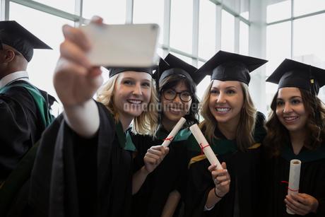 College graduates posing for selfie cap and gownの写真素材 [FYI02275694]