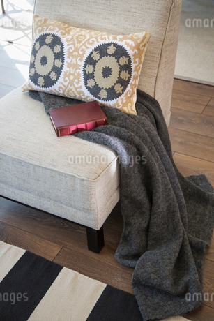 Pillow, blanket and book on chairの写真素材 [FYI02275761]