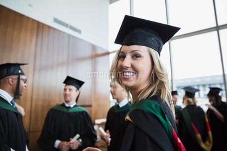 Portrait confident college graduate in cap and gownの写真素材 [FYI02275774]