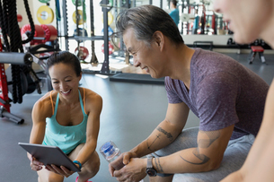 Personal trainer digital tablet talking to man gymの写真素材 [FYI02275784]