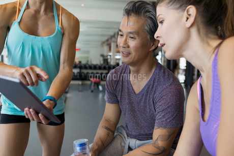 Personal trainer digital tablet talking to people gymの写真素材 [FYI02275787]