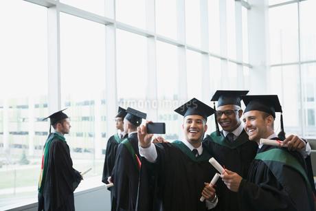College graduates cap and gown taking selfieの写真素材 [FYI02275794]