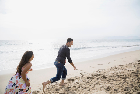 Daughter running and chasing father on sunny beachの写真素材 [FYI02275808]
