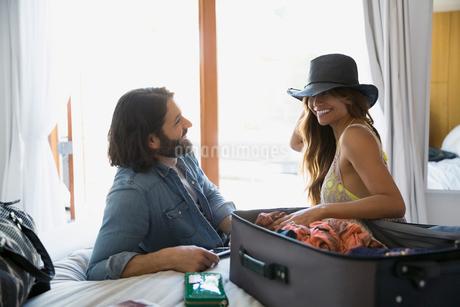 Couple unpacking suitcase in bedroomの写真素材 [FYI02275839]