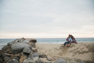Couple sitting sand hill at beach near rocksの写真素材 [FYI02275862]