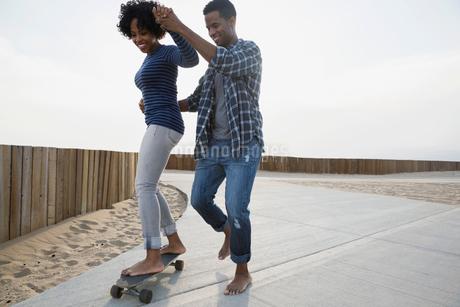 Couple skateboarding on beach pathの写真素材 [FYI02275868]