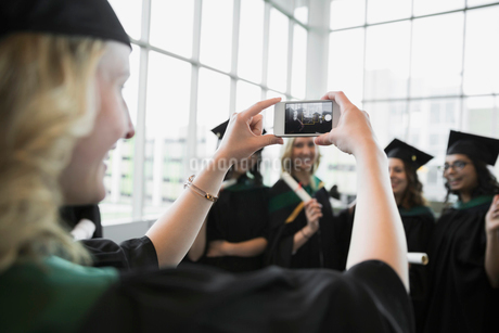 College graduates in cap and gown posing photographの写真素材 [FYI02275880]