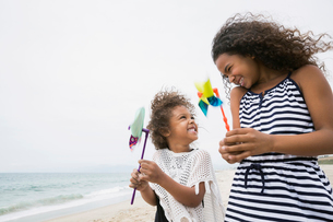 Sisters holding pinwheels on windy beachの写真素材 [FYI02275890]