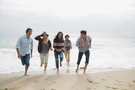 Friends running from ocean surf onto beachの写真素材 [FYI02275895]