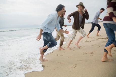 Friends running from ocean surf onto beachの写真素材 [FYI02275904]