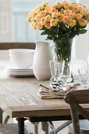 Rose bouquet and dinnerware wooden dining tableの写真素材 [FYI02275910]