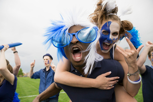 Portrait enthusiastic fans in blue piggybacking and celebratingの写真素材 [FYI02276086]