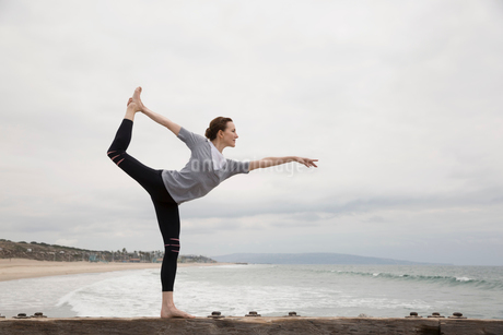 Woman doing yoga king dancer pose on beachの写真素材 [FYI02276112]