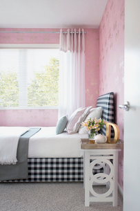 Pastel pillows on bed with gingham headboardの写真素材 [FYI02276117]