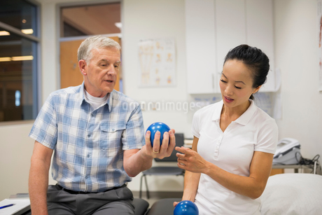 Physical therapist watching patient squeeze ballの写真素材 [FYI02276207]