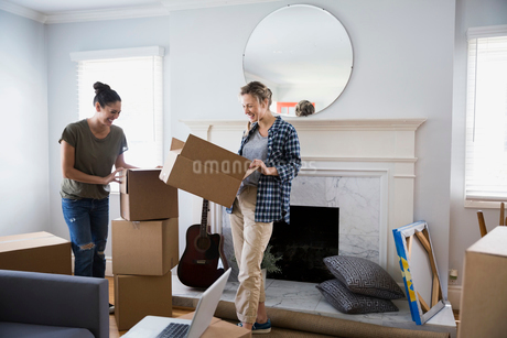 Lesbian couple unpacking moving boxes in living roomの写真素材 [FYI02276223]