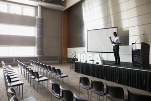 Man rehearsing on stage in empty auditoriumの写真素材 [FYI02276232]