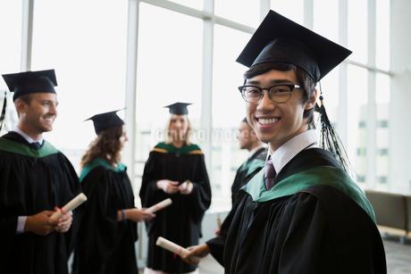 Portrait confident college graduate in cap and gownの写真素材 [FYI02276235]