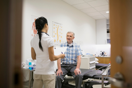 Physical therapist and patient talking in examination roomの写真素材 [FYI02276278]